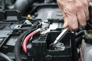 Mani che serrano il morsetto della batteria nel motore di un'automobile con una chiave